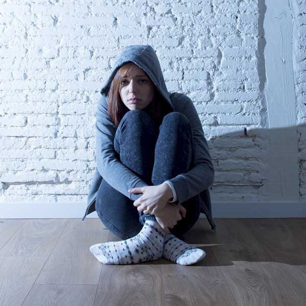 A teenage girls looks pensive and alone