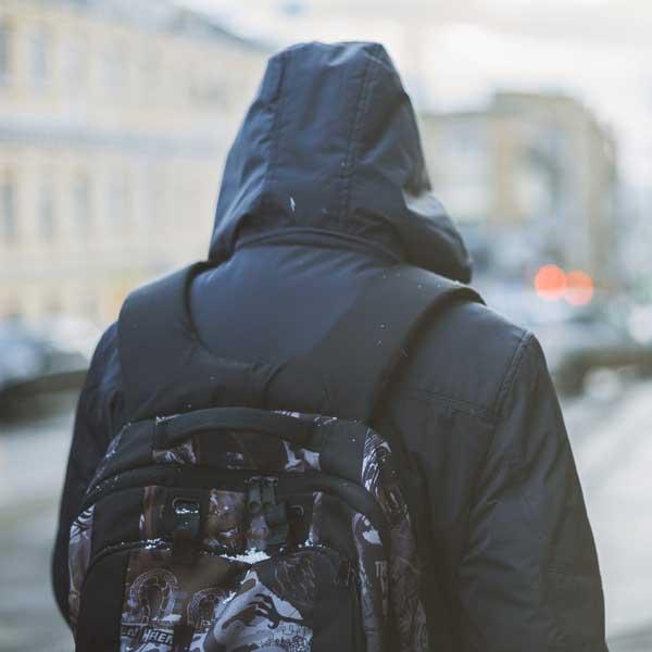 Homeless person walking down a street